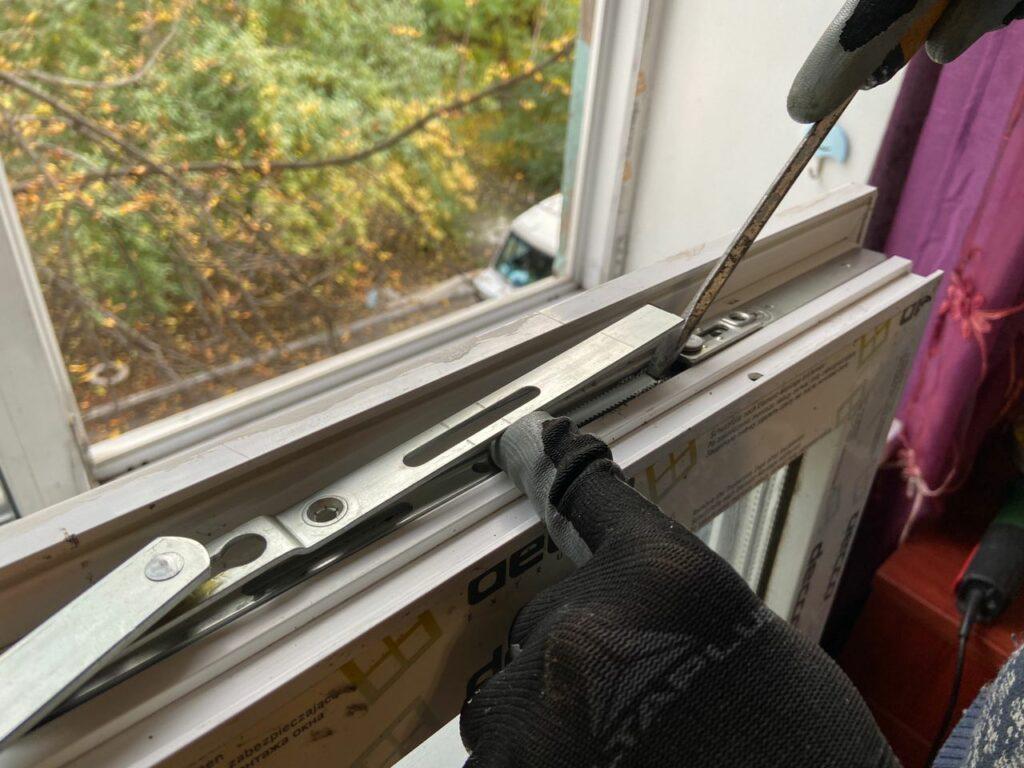 Мастер по ремонту окон устанавливает новую фурнитуру